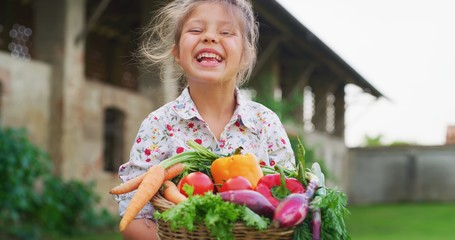 Portrait of happy little girl is holding a basket with fresh biologic just harvested vegetables and smiling in camera on a background of a countryside farm. Wall mural