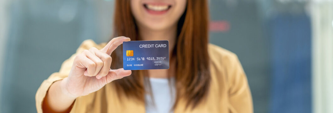 Banner of Asian woman holding and presenting the credit card for online shopping in department store over the clothes shop store, technology money wallet and online payment concept, credit card mockup