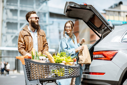Young stylish couple with shopping cart full of fresh food, packing products into the car on the outdoor parking
