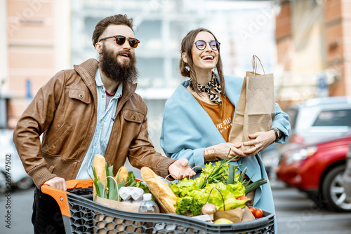 Young And Happy Couple Walking With Shoopping Cart Full Of
