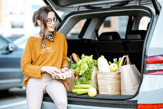 Stylish woman enjoying food while sitting on the car trunk full of healthy products on the supermarket parking outdoors