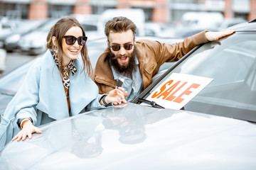 Portrait of a happy couple standing together as owners of a new car on the open ground of the dealership Wall mural