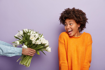 Photo of glad Afro American young woman looks happily at bouquet of flowers which man holds, receives congratulations on birthday, wears casual knitted jumper, isolated on purple background.