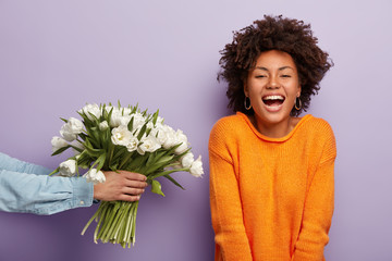 Photo of delighted African American lady laughs sincerely, gets flowers from husband or boyfriend, expresses positive emotions, wears orange jumper, stands over purple background. Happy moments