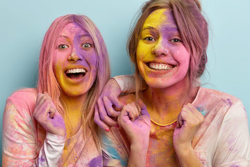 Headshot of positive cheerful two women with toothy smile on faces, have dirty colored skin, raise hands clenched in fists, celebrate annual spring Holi festival, express good emotions. Happiness, fun