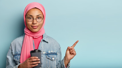 Serious beautiful Islamic woman in pink hijab, holds disposable cup of hot drink, points aside, shows direction to nice coffee shop, wears round spectacles and denim coat isolated over blue background