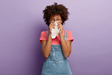 Portrait of sick African American woman sneezes in white tissue, suffers from rhinitis and running nose, has allergy on something, looks unhealthy, feels unwell. Symptoms of cold or allergy.