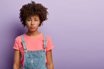 Calm attractive millennial girl with Afro aircut, dark skin, no makeup, dressed in t shirt and denim overalls, looks at camera seriously, has attentive gaze, models over purple studio wall, free space