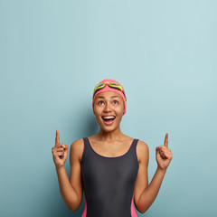 Vertical photo of joyous dark skinned female enjoys favourite hobby and summer active rest, dressed in swimsuit, goggles on forehead, points above on free space, advertises something happily
