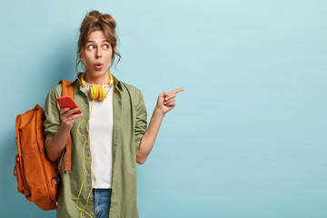 Photo of puzzled young woman holds cellular, updates application for listening favourite song from playlist, enjoys music, points away on free space, shows direction with surprised expression