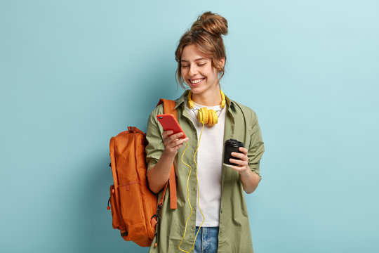 Photo of positive young woman in casual clothes, downloads multimedia file on cell phone, has headphones on neck, holds disposable cup with cappuccino, carries backpack, isolated on blue wall