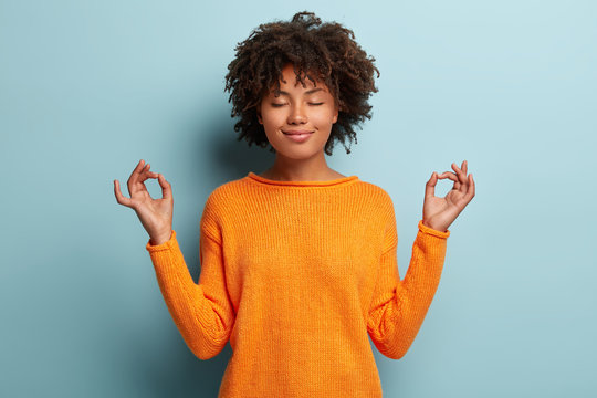 Mindful peaceful Afro American woman meditates indoor, keeps hands in mudra gesture, has eyes closed, tries to relax after long hours of working, holds fingers in yoga sign, isolated on blue wall