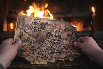Adventurer man is holding in hands a treasure map over a burning fire background. Treasure hunt concept.