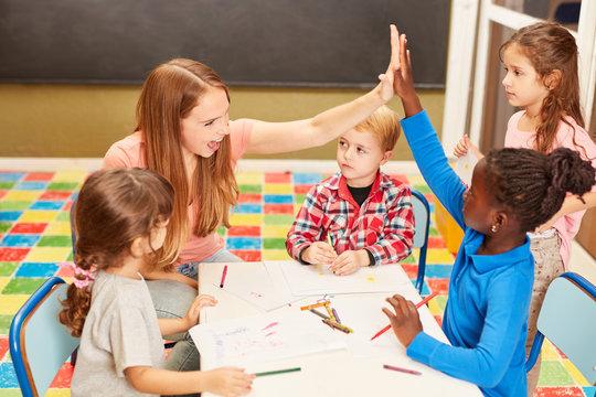 Lehrerin und Mädchen geben sich High Five