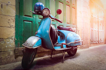 Vintage scooter stands in an alley. Post process in vintage style