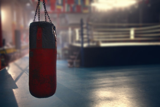 hanging red sanbag in front of boxing ring
