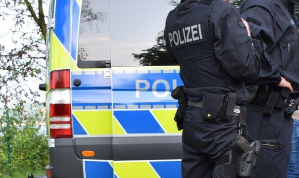 Bewaffnete Polizisten in schwarzer Uniform vor einem Polizeiauto