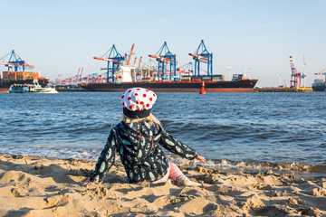 Junges Kind sitzt am Elbstrand in Hamburg mit Hafen und Schiffen im Hintergrund