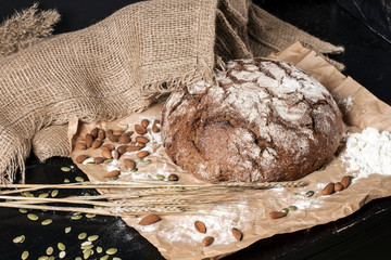 In de dag Brood freshly baked bread in flour on brown paper in combination with rye, apples, nuts and eggs. the spirit of the village.