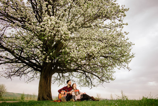 Young couple sitting under the big tree and man playing on the guitar