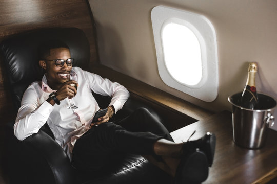 Successful young Afro American black businessman sitting in the chair of his private jet