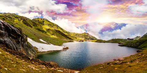 fantastic sunrise over the mountain lake. colorful clouds inthe sky gloving in sunlight. picturesque dramatic scene. majestic mountain scenery. creative artistc image