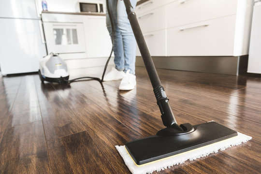 professional home cleaning service. Woman washes the floor with a steam mop