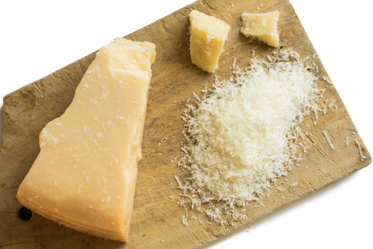 Grated parmesan cheese on white background on a wooden board