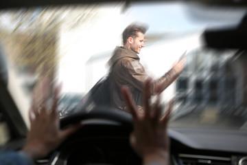 Junger Mann schaut beim Überqueren der Strasse auf sein Handy, und wir von einem Auto angefahren