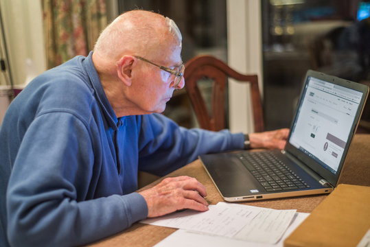 Elderly person using a laptop computer to check his share portfolios ,Hampshire,England,U.K.