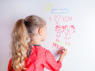 Little girl draws  family with marker on a white board.