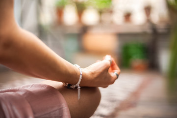 Hands asana yoga. The girl practices yoga in flowers at home close-up. Meditation, hands, bracelets handmade