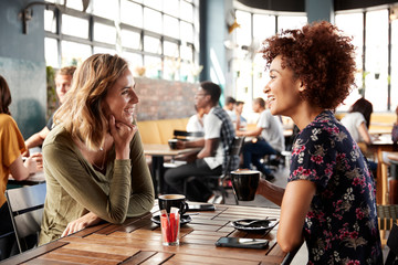 Two Female Friends Meeting Sit At Table In Coffee Shop And Talk Wall mural