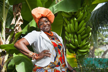 Joyful African American woman wearing a bright colorful national dress, posing in the garden near a banana tree. Traditions and fashion of Latin America, Guyana.