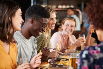 Group Of Young Friends Meeting For Drinks And Food In Restaurant