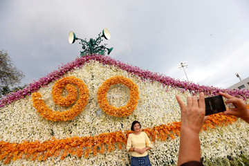 A woman poses for a picture with a floral decoration near the Grand Palace in Bangkok