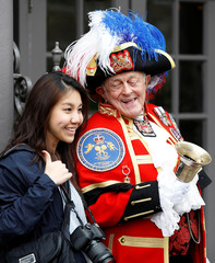 A tourist has her photograph taken with unofficial town crier Tony Appleton in Windsor