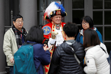Tourists take photographs of unofficial town crier Tony Appleton in Windsor
