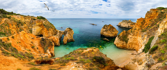 View of stunning beach with golden color rocks in Alvor town , Algarve, Portugal. View of cliff rocks on Alvor beach, Algarve region, Portugal. Wall mural