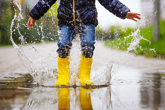 legs of child with yellow rubber boots jump in puddle on an autumn walk