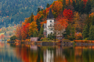 Villa Castiglioni in colorful forest reflected in water, lake Grundlsee