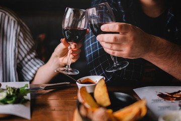 Glasses of red wine with food on table. Selective focus, couple toasting with glasses of red wine in the restoran. Blurred abstract background of clinking glasses of wine. Selective focus. Toned image