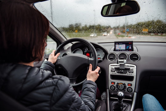 Woman driving car on a rainy day