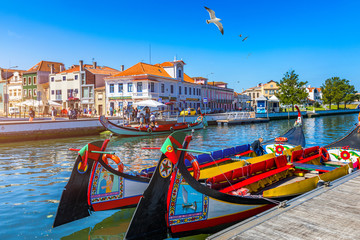 Traditional boats on the canal in Aveiro, Portugal. Colorful Moliceiro boat rides in Aveiro are popular with tourists to enjoy views of the charming canals. Aveiro, Portugal. Wall mural