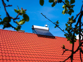 Solar water heater boiler on rooftop, green defocused leaves, conceptual green house image.