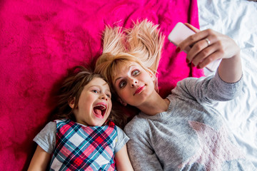 Mother and daughter have a fun making a selfie with mobile phone