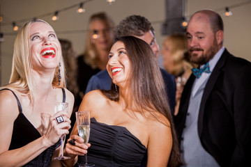 Two Laughing Women Being Watched by Men at Party