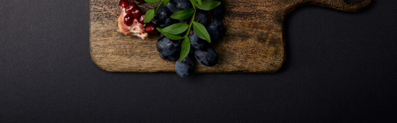 panoramic shot of cutting board, grapes and garnet on black surface