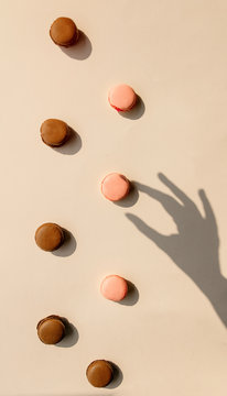 Chocolate and strawberry macrons and shadow of female hand