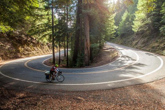 Women climbing hairpin turn mountain road on cross country bike.